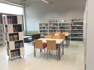 Kuvassa kaupunginkirjaston lukunurkka. Pöytiä, tuoleja ja kirjahyllyjä.