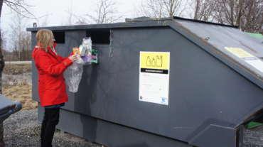 Jätteiden lajittelua keräyspisteeseen